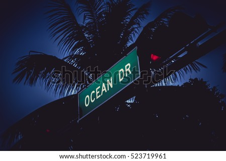 Ocean Drive sign with palm trees at dusk, Miami Beach. Vintage colors