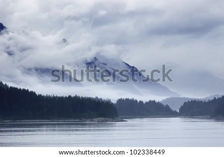Ocean, Land, Mountain and Sky in Alaska A photo taken from a cruise ship at Alaska, USA. - stock photo