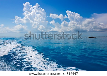 ocean landscape with turquoise water,  beautiful clouds and small fishing  boats - stock photo
