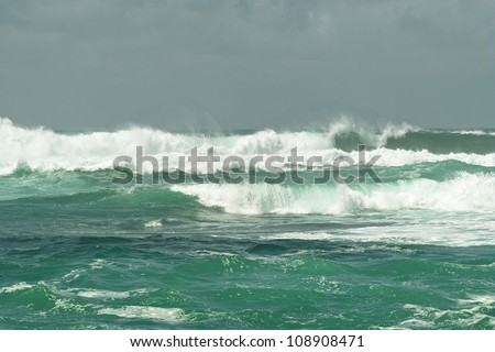 Ocean light green surf waves with white horses near the shore - stock photo