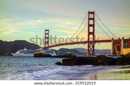 Ocean liner sailing under the Golden Gate Bridge, photographed from Baker Beach. - stock photo