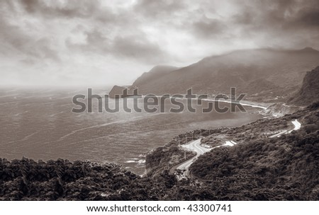 Ocean of bay with forest and roads in the cloudy sky. - stock photo