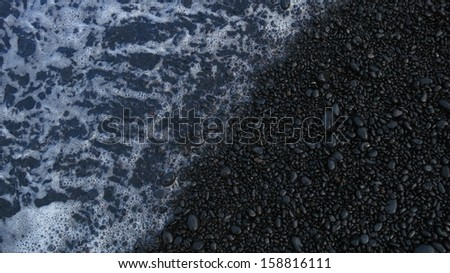 Ocean on a black sand beach - stock photo