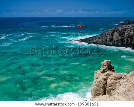 Ocean rocky shore and red coastguard boat on green waves. - stock photo