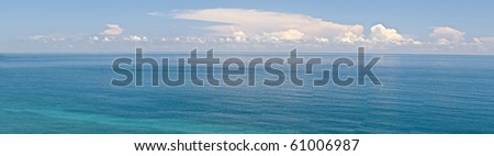 Ocean scenery in panorama in daytime under blue sky. - stock photo