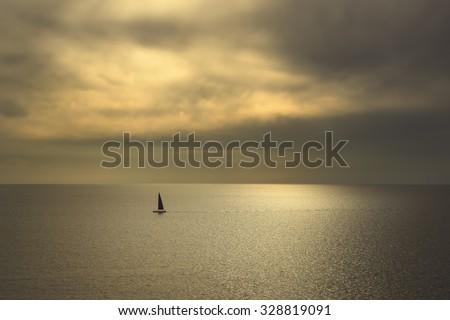 Ocean sea sunset view and black sail boat. Mediterranean sea. Tuscany, Italy - stock photo