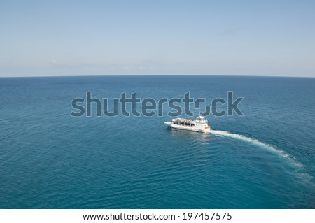 Ocean shuttle transporting passangers to land on a calm blue ocean - stock photo
