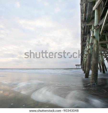 ocean sunrise by pier - stock photo