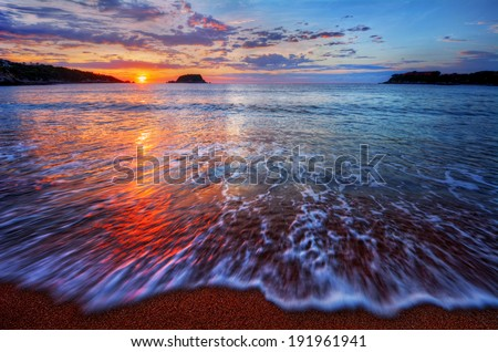 Ocean sunrise with bright clouds and dynamic breaking wave - stock photo