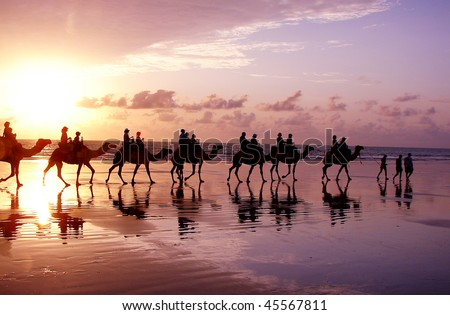 Ocean Sunrise with people and camels - stock photo