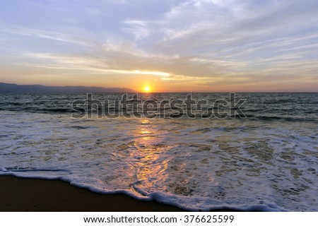 Ocean sunset is brightly light golden seascape with a gentle wave rolling to the shore. - stock photo