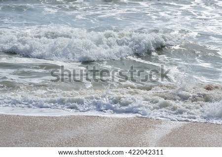 Ocean Surf waves and foam on the beach - stock photo