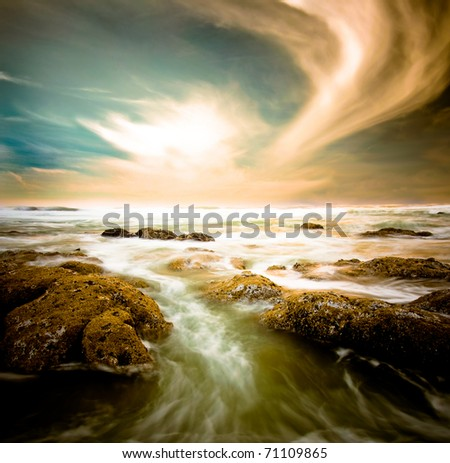 Ocean surge with rocks under a dramatic sky. - stock photo
