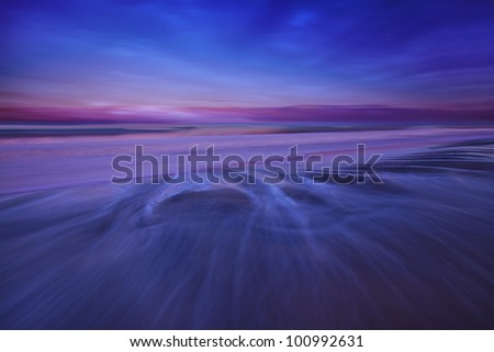 Ocean tide waves and storm clouds at sunset over beach - stock photo