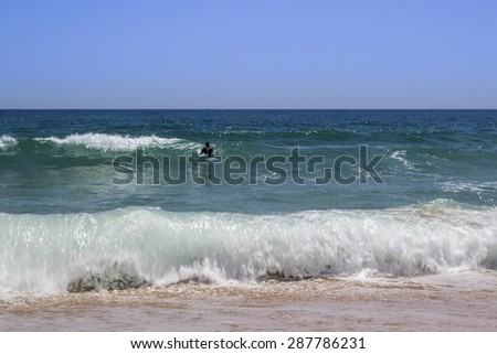 Ocean view and people surfing in Tavira Island coast beach, Algarve, Portugal.