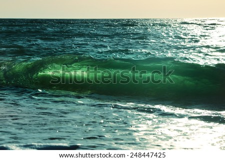 Ocean-view design postcard. Beautiful colorful breaking surfing ocean wave rushing at sunset time  - stock photo
