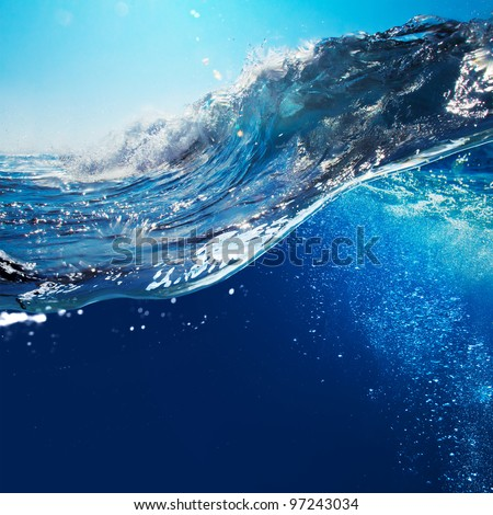 ocean-view seascape landscape with blue sky and sunlight big curly ocean wave splitted by waterline to underwater part with air bubbles