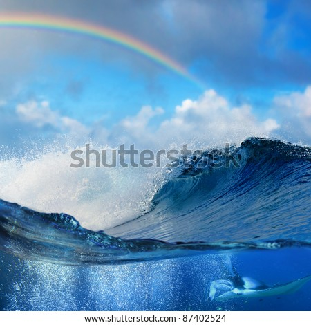 Ocean view splitted underwater side with mantaray surrounded by air bubbles and shore break big waves with colored rainbow - stock photo