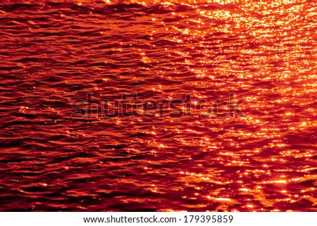 Ocean water surface texture red tinted - stock photo