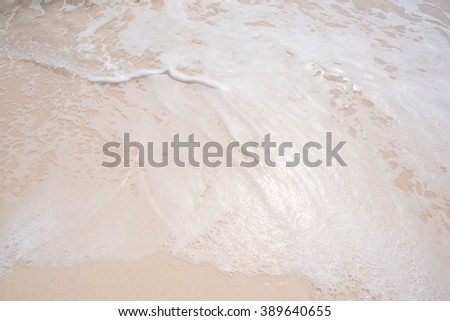 Ocean water washes over a sandy beach - stock photo