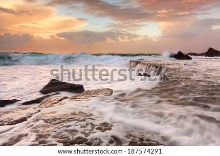 Ocean waterfalls, large waves,  fast flowing water and lots of sea foam at a peachy sunrise morning.  Forresters Beach NSW Australia - stock photo