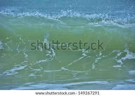 Ocean wave begins to fall as wind sprays edge, reflection, blue, green, aqua - stock photo