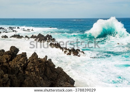 Ocean wave breaking the sea water on the rocky shore line, with water foam and blue sea water on the background. Porto Moniz, the northwest corner of the Madeira island, Portugal. - stock photo