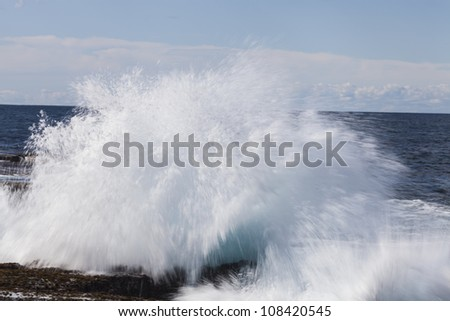Ocean wave crashing onto the rocks in an explosive way