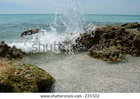 Ocean wave splashing into rocks along the shore. - stock photo