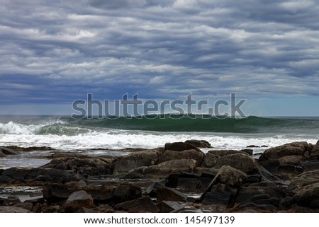 Ocean waves against a rocky shore. - stock photo