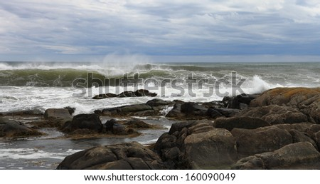 Ocean waves breaking on rocks - stock photo