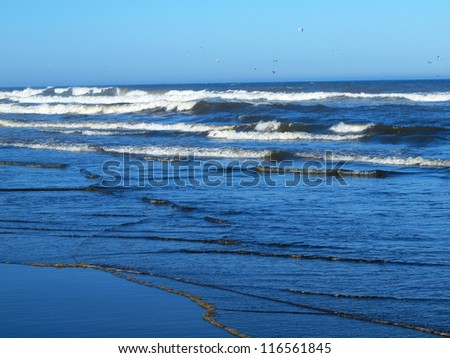 Ocean Waves Breaking on Shore on a Clear, Sunny Day - stock photo