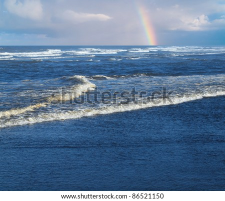 Ocean Waves Breaking on Shore with a Partial Rainbow in the Background