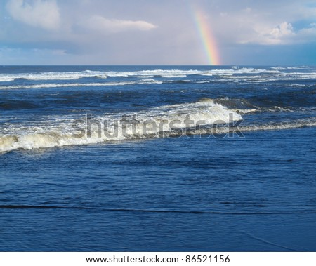 Ocean Waves Breaking on Shore with a Partial Rainbow in the Background - stock photo