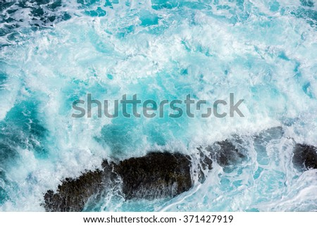 ocean waves crashing on the rocks with white foam - stock photo