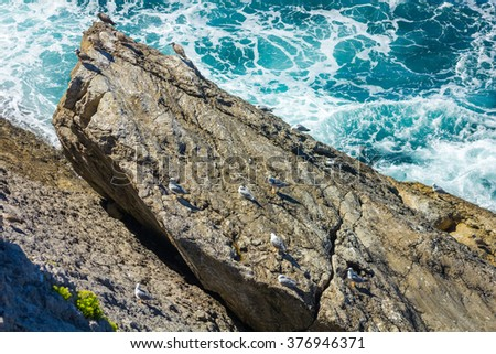 ocean waves crashing on the rocks with white foam - stock photo