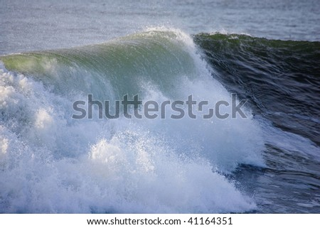Ocean Waves curling as they approach the shore - stock photo