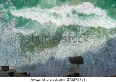 Ocean waves shot from above. The water is turquoise color and you can also see a rock. You can also see the shore and sand.  - stock photo