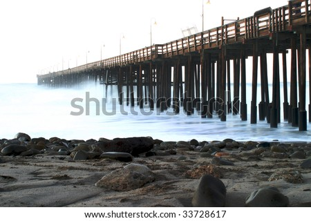 Ocean waves throughout at storm crashing into a wooden pier. - stock photo