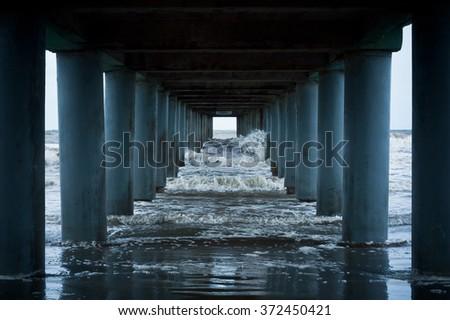 Ocean waves under the piers pillars - stock photo