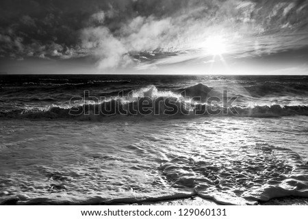 Ocean waves with a sunburst and lens flare on a windy day in black and white. - stock photo