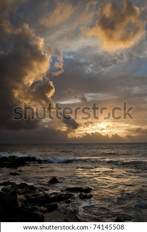 Ocean with a golden sunset shining through the Hawaii clouds - stock photo