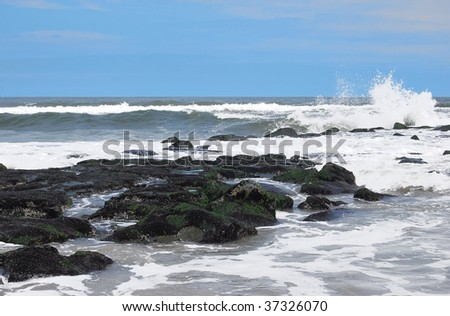 Ocean with rock jetty and splashing wave - stock photo