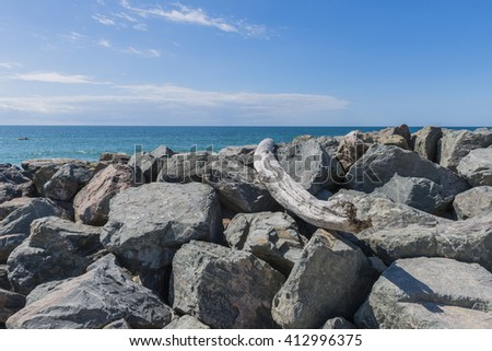 Ocean with shore protection of rocks and a canoe on the water.