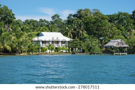 Oceanfront property with a Caribbean house and a tropical hut over the water, Bocas del Toro, Panama, Central America - stock photo