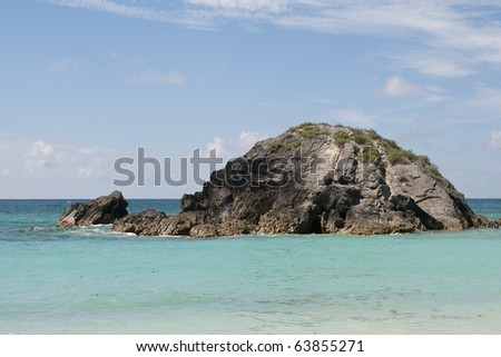 Oceanic Beach scene with large rock island in view surrounded by beautiful clear blue water