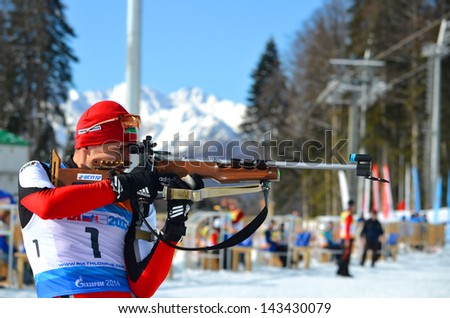 "OCHI, RUSSIA - FEBRUARY 9: Sergey Balandin competes in IBU Regional Cup in Sochi on February 9, 2013. The combined ski-biathlon complex ""Laura"". Men's Pursuit firing line. - stock photo"