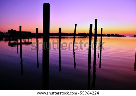Ocracoke Harbor at sunset with pier pilings silhouettes - stock photo