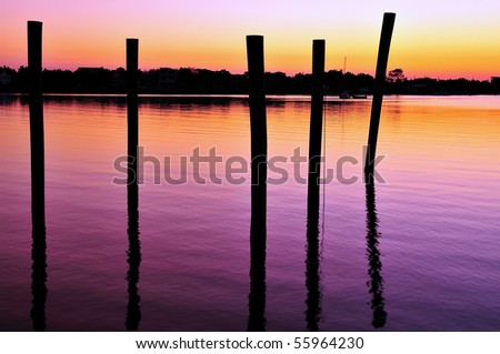 Ocracoke Harbor at sunset with pier pilings silhouettes