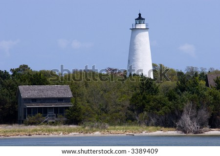 Ocracoke Lighthouse Shoreline   Built in 1823, the Ocracoke Lighthouse is the oldest active lighthouse in North Carolina. Located in a fishing village on Ocracoke Island. - stock photo